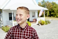 Boy smiling, country home in the background