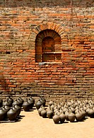 Many clay vases kept for drying with brick wall