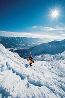 Skier carrying skis up rugged snowy mountain