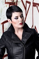 Sexy brunette young woman in a leather jacket over urban backgro