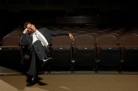 Businessman napping on theater seat