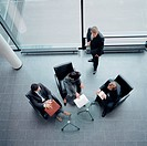 Four Businesspeople Conferring in Office Building