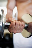 Man Exercising With Weights in Gym