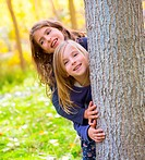Autumn sister kid girls playing in poplar tree forest near trunk in nature outdoor
