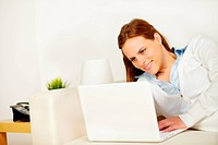 Cheerful woman lying on sofa with a laptop