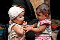Muslim women stand in a queue with their children at a pulse polio drive at Baiganwadi , Govandi , Bombay now Mumbai , Maharashtra , India