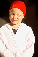 Smiling girl wearing bathrobe and swimming cap