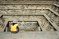 Woman sitting along Pushkarani (Stepped well) ; Hampi Vijayanagar ruins ; Karnataka ; India