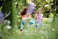Rear view of three girls running in a garden