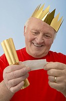 Portrait of an aging man wearing a paper crown and looking at the joke inside his Christmas cracker