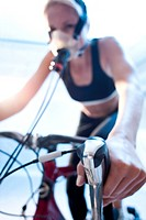 MODEL RELEASED. Performance testing. Athlete riding an exercise bike while her performance and oxygen consumption are measured.