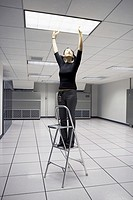 Woman reaching ceiling light with step ladder