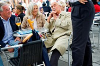 Vienna, Austria. Two men and a woman drinking at table outside