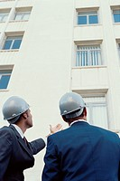 Two men wearing hard hats having a conversation