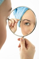 Young Woman Holding Hand Mirror and Plucking Eyebrows