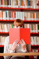 Girl hiding behind the book on library