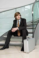 Businessman Sitting on Staircase