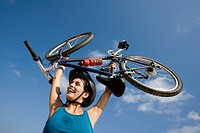 Woman lifting a bicycle over her head