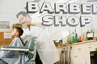 Hairdresser cutting boy's hair