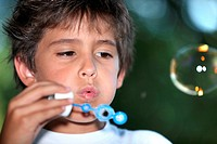 Young child blowing bubbles