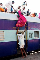 Old man helping woman trying to climb on roof of train on railway station ; Jodhpur ; Rajasthan ; India