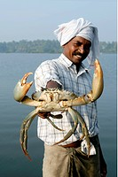 A happy fisherman with his catch giant size crab , Cherai backwater , Kerala , India NO MR