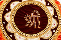 Maroon coloured velvet cloth decorated circular form of golden border and peals Shri mentioned in centre , Pune , Maharashtra , India