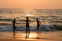 Children playing with sea waves ; sunset at Sagreshwar beach ; Vengurle ; Sindhudurg district ; Maharashtra ; India