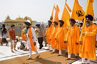 Orange color dressed Sikh men taking out the procession on the occasion of Guru Ramdas Jayanti out side Akal Takht ; Swarn Mandir Golden temple ; Amri...