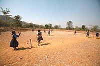 School girls in uniform playing cricket in dry fields in Jharkhand , India