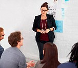 A female designer listening to her colleagues, while standing in front of a board