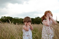 Two little girls playing hide and seek in a field