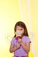 A Little Girl Wearing Fairy Wings Holding a Star Shaped Cake Pop with Colored Sprinkles