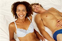 High angle portrait of a couple laying on a bed in their underwear