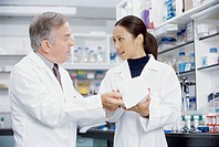 View of two scientists talking in lab setting