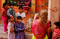 Female foreign tourist taking picture of children on occasion of Shivratri ; Jodhpur ; Rajasthan ; India MR704