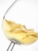 A glass of white wine being swirled