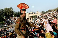 Indian Border Security Force soldier helping audience before retreat ceremony called lowering flags at India-Pakistan international border ; Wagah bor...