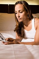 Woman Lying on Bed Using Cell Phone