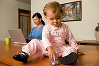 Mother Using a Laptop While Baby Plays with a Cell Phone