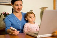 Mother with Baby Using a Laptop and Listening to Music