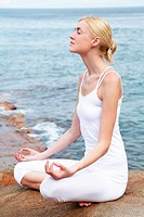 Young woman meditating outdoors by the sea