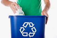 Man placing glass jar into recycling bin