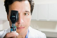 Doctor looking through ophthalmoscope