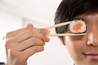 Young Asian businessman holding sushi in his chopsticks