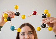 Young woman holding molecules model