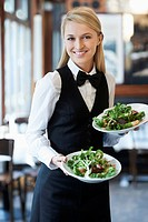 Portrait of young waitress holding plates with salad