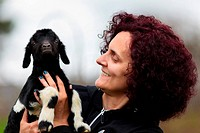 Woman holding a baby goat