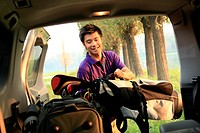 young man putting bags in car trunk