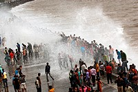 People enjoying hightide waves at marine drive ; Bombay Mumbai ; Maharashtra ; India  24-July-2009